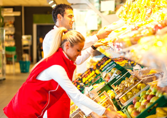Two supermarket workers standing by the grocery shelf and selecting goods
