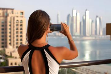 Beautiful travel woman taking photo photographing using smart ph