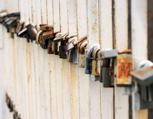 Steel locks hanging on a bridge made by loving couples as a tradition