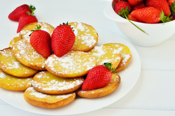 Poster Dessert Pancakes with powdered sugar decorated with whole strawberries on a white plate on a white table