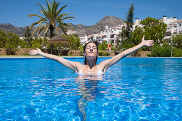 brunette vacation smiling woman with white bikini looking and arms up outstretched gesturing victory or greeting in blue water of swimming pool
