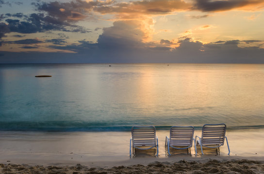 Empty Chairs on the shore at Sunset. Seven mile beach, Grand Cayman