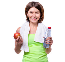 sport girl holding apple and water with towel on her neck isolated on white background