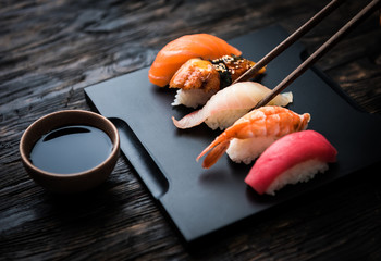 Printed kitchen splashbacks Sushi bar close up of sashimi sushi set with chopsticks and soy on black background