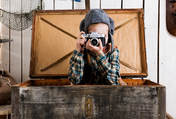 little girl in pilot hat in wooden chest taking ptoto with rarity camera