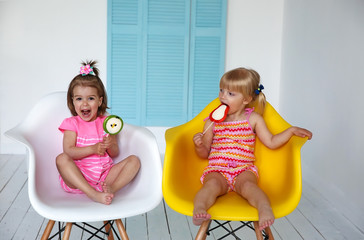 little girls sitting in chairs and eating candy sticks