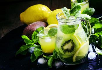 Refreshing summer cocktail with green basil, lemon, kiwi fruit a