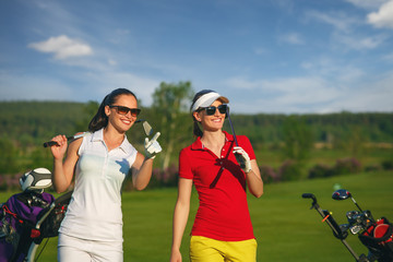 Two smiling sportive women golfers walking on golf course at sunny day