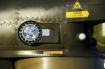 Headlight of military helicopter on armored side of green combat flying vehicle with rivets, air force, modern aviation and aerospace industry