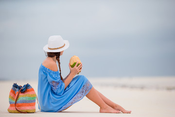 Young woman drinking coconut milk on the beach
