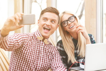 Pretty guy and girl are taking photo on telephone
