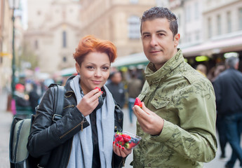 Cheerful couple eating strawberries