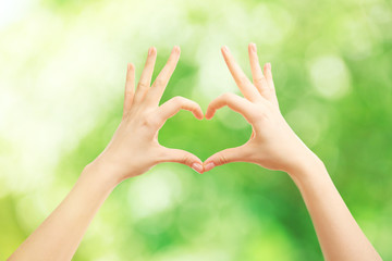 Female hands in shape of heart, on green nature background