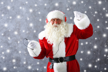Santa Claus with headphones listening to music on gray wall background with snow effect
