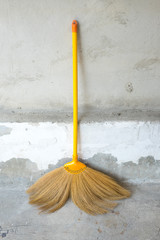 lonely broom with cement wall