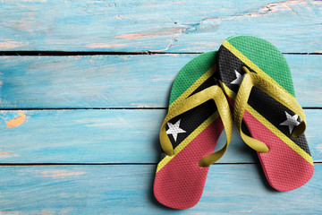 Thongs with flag of Saint Kitts and Nevis, on blue wooden boards