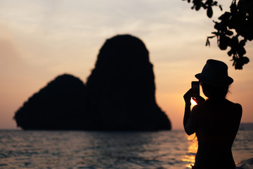 Silhouette of a girl who photographed the sunset on the beach in