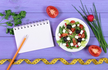 Greek salad with vegetables, tape measure and notepad for writing notes, concept of slimming, healthy lifestyle and nutrition