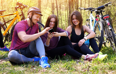 Two females and one male using smartphone in a park.