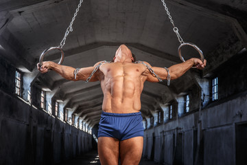 Man workouts in the air with gimnastic rings.