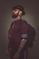 Tattooed bearded man with backpack.