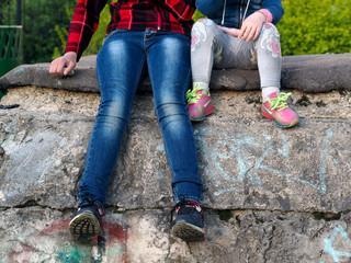Legs of children on the background of the old concrete wall. Jeans, sneakers. Large and small child.