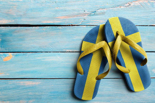 Thongs with flag of Sweden, on blue wooden boards