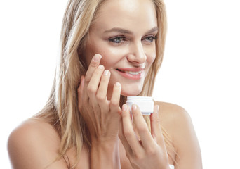 beautiful young woman smiling while adding facial cream