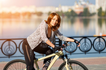 Young redhead woman riding a bike on embankment. Active people outdoors. Sport lifestyle.