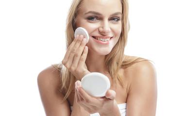 beautiful blonde woman applying face powder