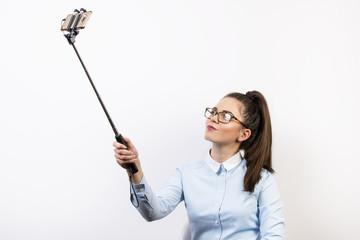 Fototapeta Młoda kobieta robi sobie zdjęcia ze selfiesticka obraz