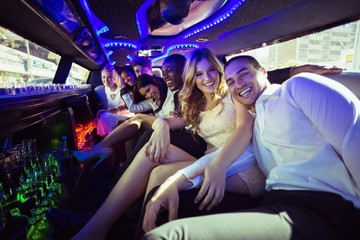 Happy friends chatting in limousine