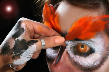 Girl in the mask of an owl, body art