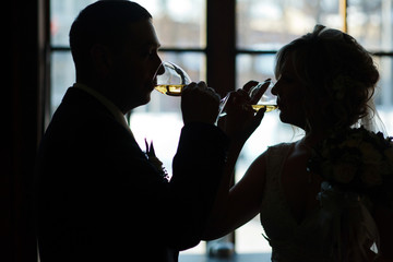 A silhouette of bride and groom drinking a sparkling champagne i