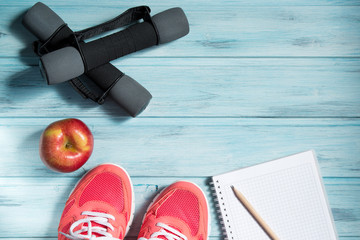 Fitness concept, pink sneakers, red apple, dumbbells and notebook with pencil on wooden background, top view