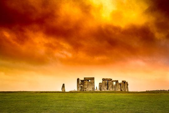 Stonehenge under stormy red orange and yellow sunset sky.