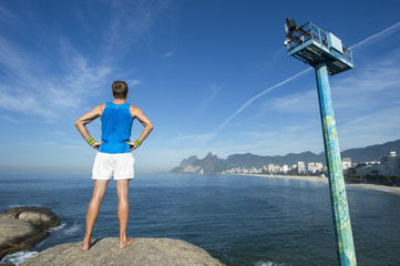 Athlete standing in front of the Rio de Janeiro skyline at Arpoador, Ipanema Beach