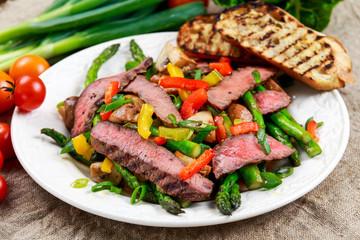 Grilled steak with stir-fried vegetables on plate.