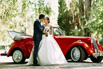 Couple on the wedding and a car on the background
