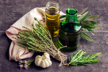 Herbs: rosemary, thyme, bottles of olive oil and garlic