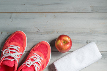 Fitness concept, pink sneakers, red apple and white towel on wooden background, top view
