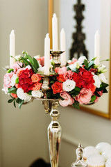 White candles and bouquet of colorful flowers
