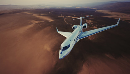 Image of White Luxury Generic Design Private Jet Flying in Sky under the Earth Surface. Uninhabited Desert Mountains Background. Business Travel Picture. Wide, side view. Film Effect. 3D rendering.