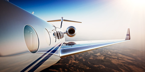Photo of White Luxury Generic Design Private Jet Flying in Blue Sky at sunset.Uninhabited Desert Mountains Background.Business Travel Picture.Horizontal,Film Effect. 3D rendering.