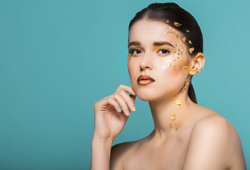 Portrait of a beautiful young woman with bright golden make up