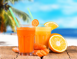 Fresh juice orange and carrot on wood with tropical beach background