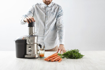 Focused on carrots. Unrecognizable man presses carrots inside metallic professional juicer to make tasty juice for breakfast from fresh carrots, pours in transparent glass. All lying on wooden table.