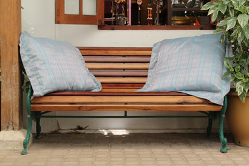 Wooden bench with blue pillows with white wall.