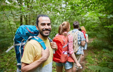 group of smiling friends with backpacks hiking