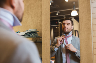 man tying tie on at mirror in clothing store